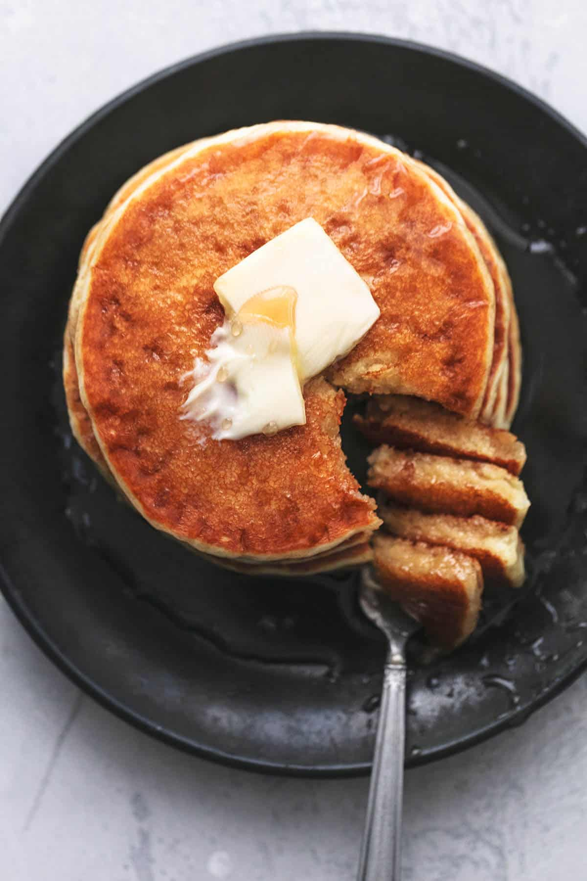 Beißen Sie aus einem Stapel Pfannkuchen auf einem Teller mit Butter und Sirup
