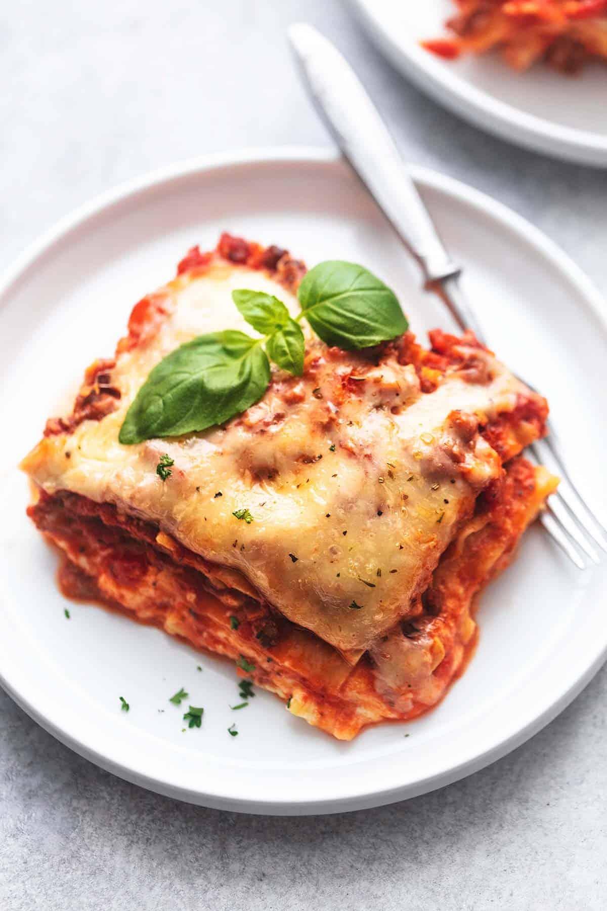 hautnah ein Stück Lasagne mit Basilikum auf einem weißen Teller mit einer Gabel