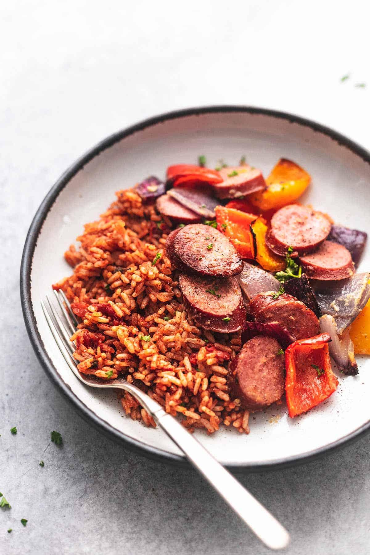 Wurst und Gemüse und Reis auf einem Teller mit einer Gabel