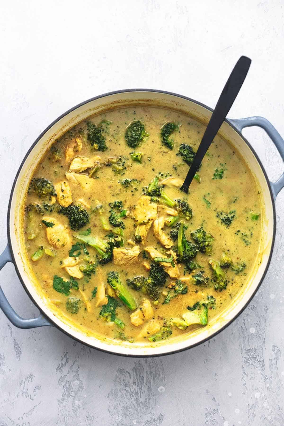 Huhn und Curry mit Brokkoli in einem Topf mit einem Löffel