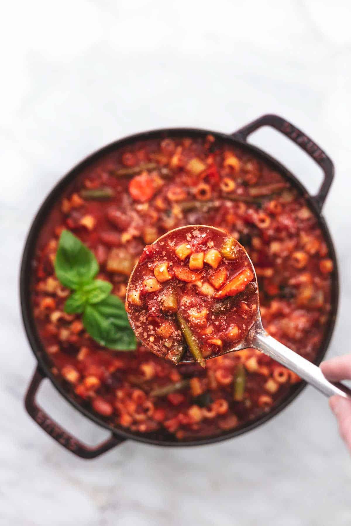 Schöpflöffel voller Minestrone-Suppe über einen Topf Suppe