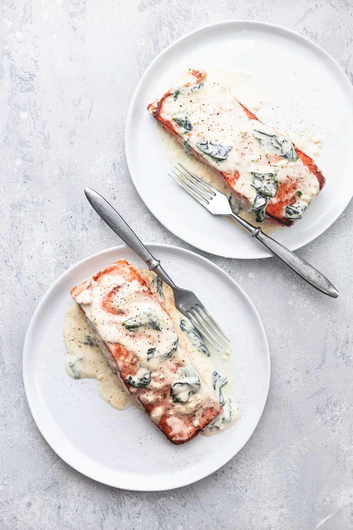 Lachs Florentiner mit einer Gabel auf zwei Tellern