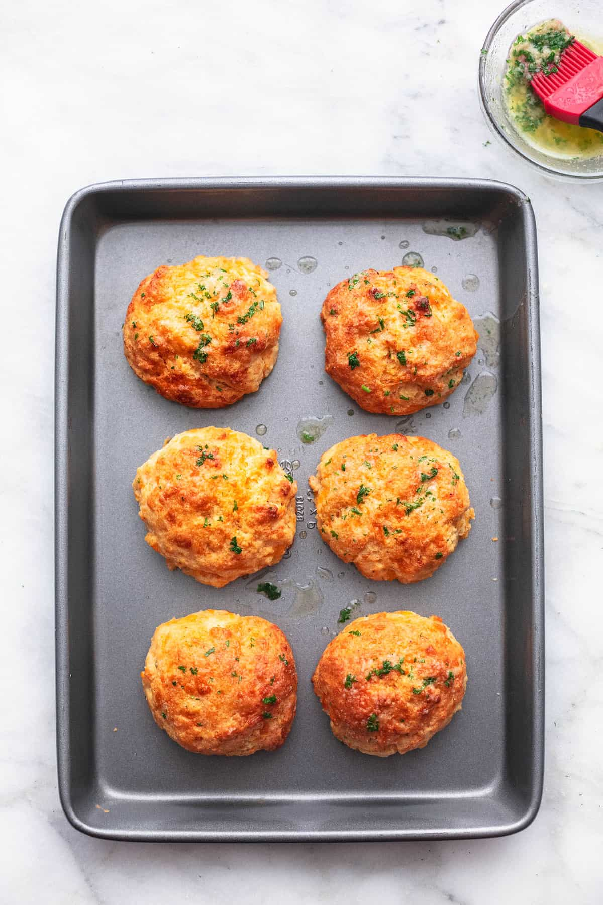 red lobster cheddar bay biscuits on a baking pan with butter sauce in a bowl